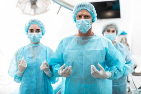 Cirujano y sus asistentes en batas azules estériles de pie en el quirófano