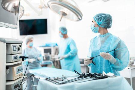 Joven enfermera sosteniendo un instrumento laparoscópico y mirando a sus colegas