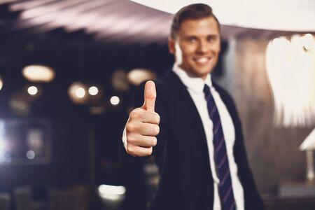 Selektiver Fokus eines gutaussehenden Mannes, der lächelt und seinen Daumen hochlegt