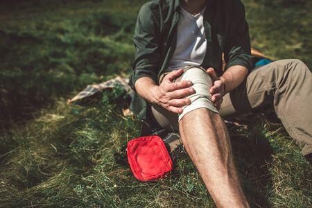 Traveler man making bandage of his leg himself