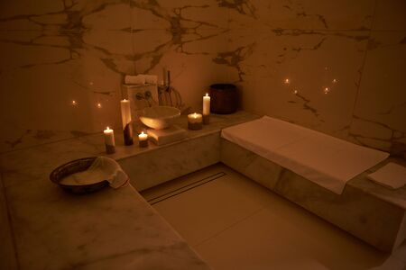 Side view of the Turkish bath with white towels and candles Banque d'images - 131804542