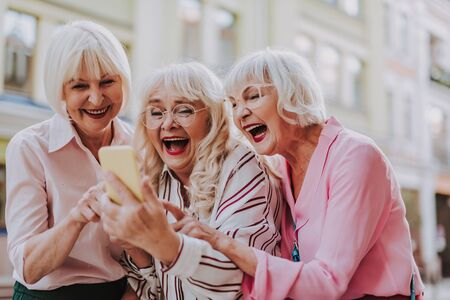 Three old females looking at the phone and laughing