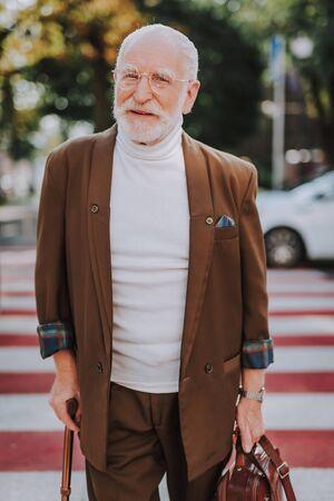Stylish cheerful old man walking across the street