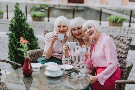 Three beautiful ladies holding cups of tea
