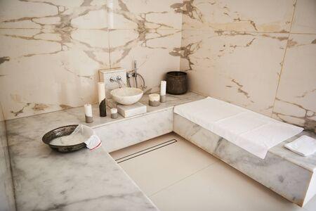 Photo minimaliste de bain turc en marbre avec serviettes et bougies