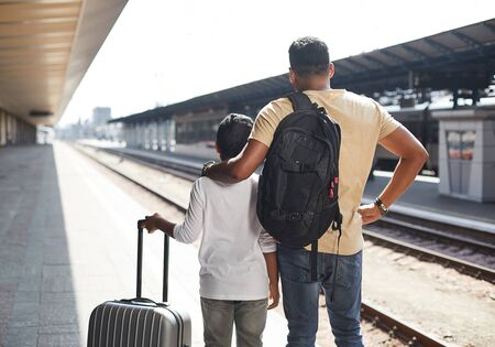 Rear view of loving father and his son at the railway station