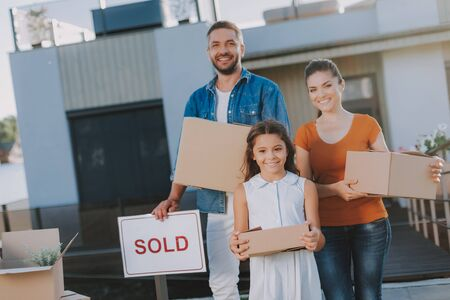 Positive nice family standing near their sold house