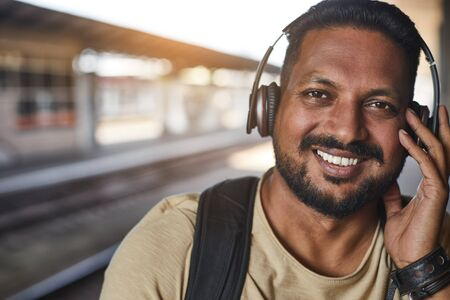 Portrait of a hindu smiling man listening to music