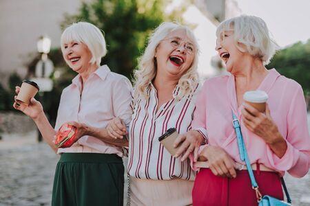 Three stylish old women make fun together