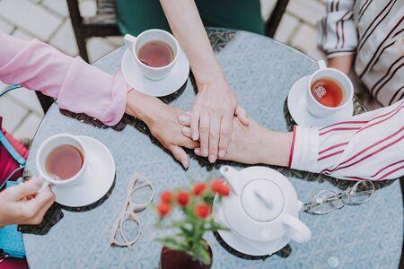 Three female hands are on the table