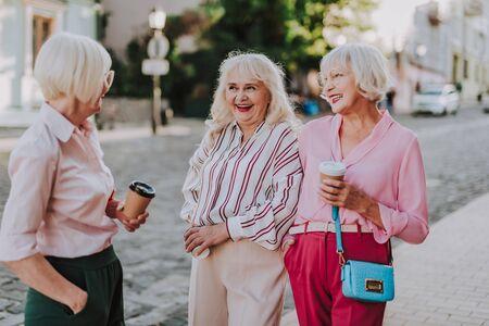 Three smiling elderly women are communicating on road