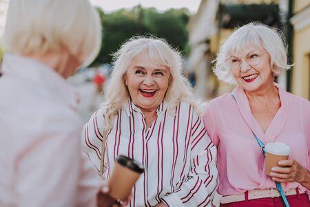 Happy older women meeting their female friend on the street