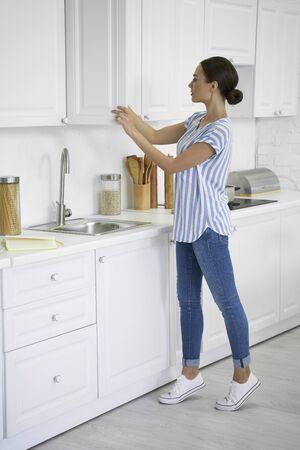 Woman in the white kitchen interior stock photo