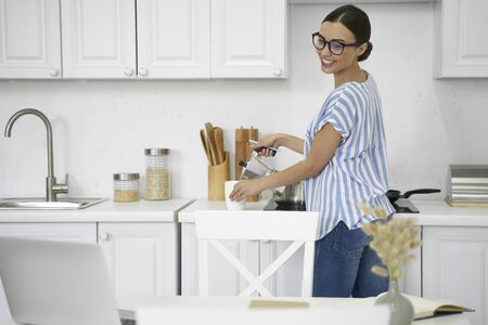 Gladsome lady looking at laptop and pouring coffee stock photo