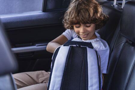 Happy kid is looking at his schoolbag
