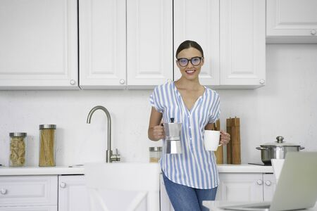 Happy woman with coffee in the kitchen stock photo