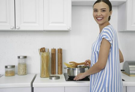Positive woman stirring spaghetti and smiling stock photo