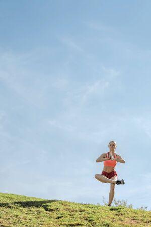 Young harmonious lady in yoga pose outdoors 版權商用圖片