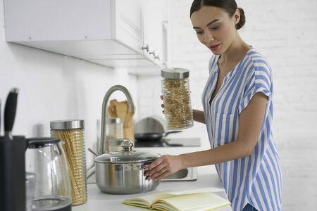 Woman with spaghetti reading the recipe stock photo Stok Fotoğraf