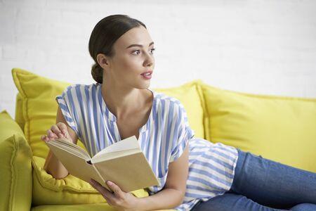 Woman with book looking away stock photo Фото со стока