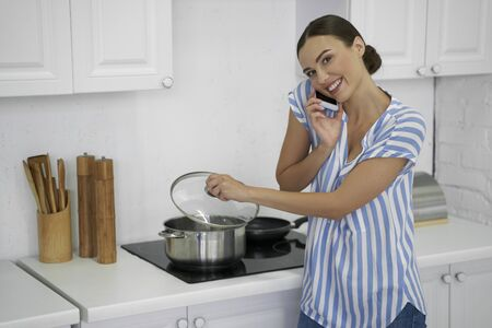 Cooking meals and having phone talk stock photo