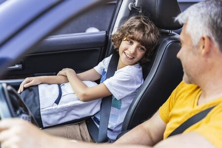 Little boy looking at his mature father in the car