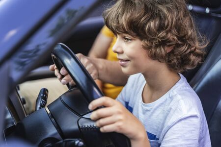 Happy little driver looking at road in the car