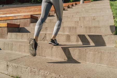 Close up of sportive lady running up on steps