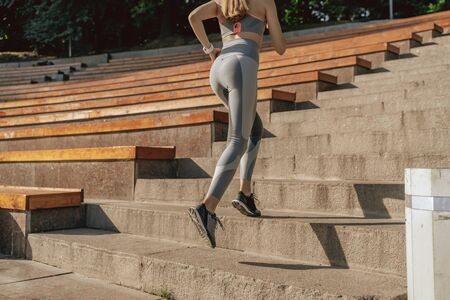Sportive young lady running up on steps