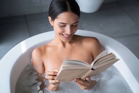 Happy lady reading a book in the bathroom