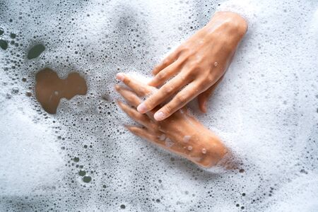 Young woman hands splashing in the water