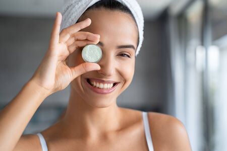 Smiling young woman with an eye cream