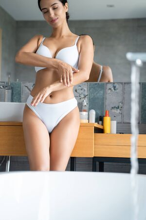 Slim female rubbing a moisturizer in the bathroom Zdjęcie Seryjne