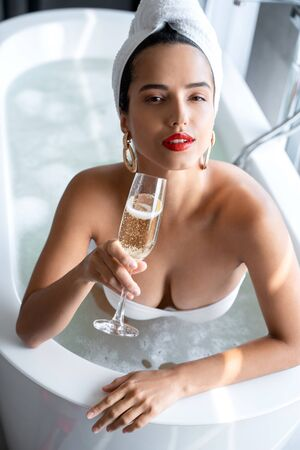 Woman sitting in a bath with a glass of champagne