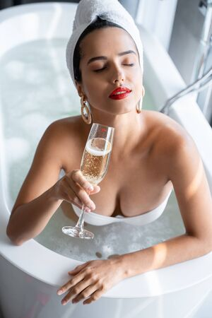 Woman sitting in a bathtub with a fizzy beverage Imagens