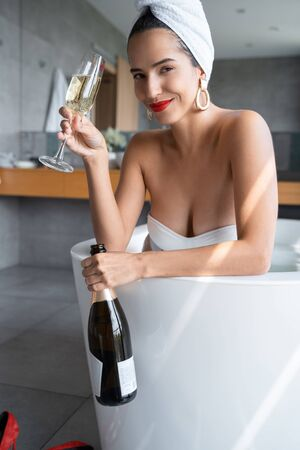 Woman taking a bath with a bottle of champagne