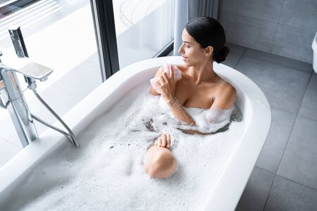 Relaxed female with a sponge in the bathtub