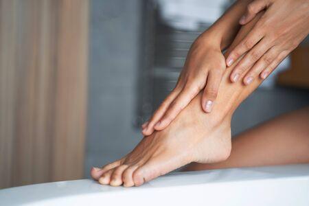 Woman applying a moisturizer on her legs