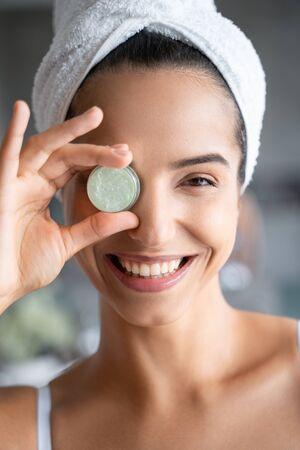 Cheerful cute girl holding her eye cream