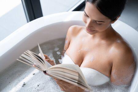 Smiling young woman sitting in the bathtub Zdjęcie Seryjne