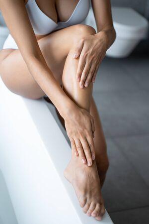 Caucasian woman applying a moisturizing body cream