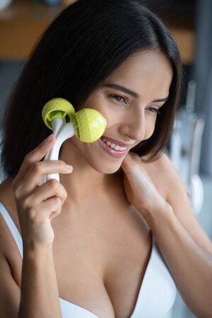 Happy good-looking young female using a massage roller
