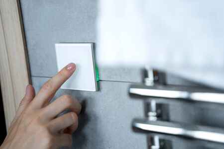 Hand turning on the light in the bathroom