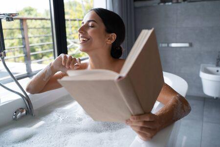 Joyful young lady sitting in a bath Imagens