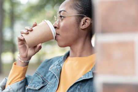 Young woman sipping hot drink outdoors stock photo