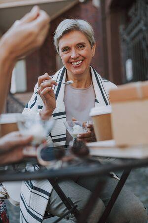 Cheerful woman enjoying a vanilla dessert in a cafe