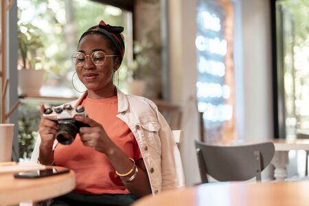 Smiling trendy woman with camera in restaurant stock photo
