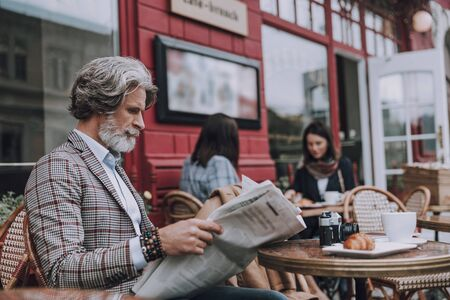 Man with camera and croissant reading the news stock photo Imagens