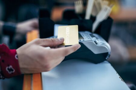 Man with kerchief on wrist is holding credit card for buying something in shop. Website banner Stock fotó