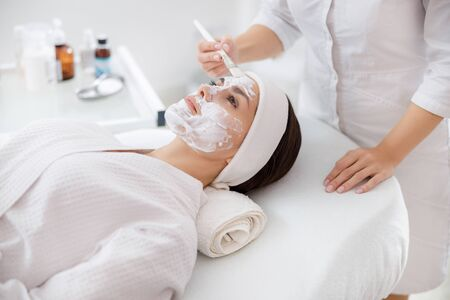 Beautician applying cosmetic mask on lady face